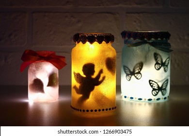 Diy Fairy Jar on white brick wall background. Gift ideas, decor St February 14, Valentines Day, love, wedding. Handmade Lamp, night light, lantern from glass jar, napkin, glue, glitter