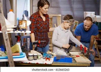 Diy family tinkering in workshop, little boy using saw.