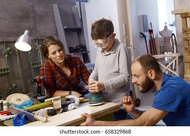 Diy father teaching son to use jigsaw in workshop.