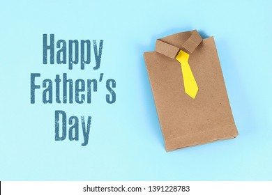Diy fathers day gift bag package shirt with necktie crafting paper on a blue background. Gift idea, decor father day. Top view. father shirt. Dad tie.