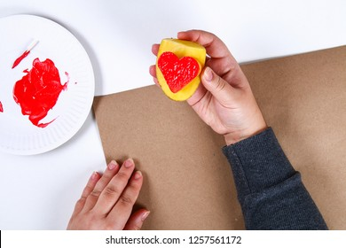 Diy. Gift wrapping for Valentine's Day. Kraft paper gift and potato stamp in the shape heart and red paint do it yourself on February 14th. Top view on a white background. step by step. Handicraft