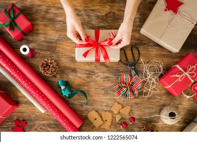 DIY Gift Wrapping. Woman wrapping beautiful christmas gifts on rustic wooden table. Overhead view of christmas wrapping station.