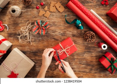 DIY Gift Wrapping. Woman wrapping beautiful red christmas gifts on rustic wooden table. Overhead point of view of christmas wrapping station.