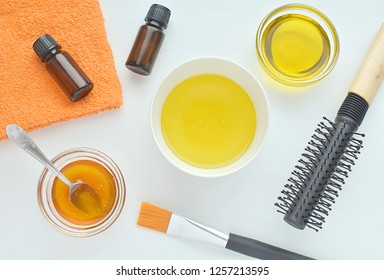 Diy hair mask with natural ingridients, honey olive oil, essential oils, cosmetic brush, hair brush, flat lay.