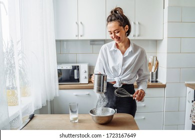 DIY home cooking concept. A bright brunette woman sifting the flour for pancakes through a sieve, salting the dough, adding milk. Young woman smiling, loves to cook in a beautiful modern kitchen.