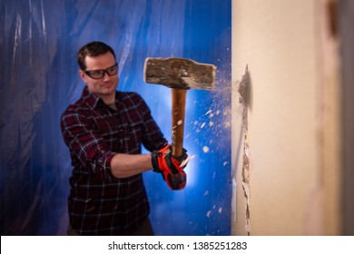 Diy home demolition man smashes hole in wall with sledgehammer