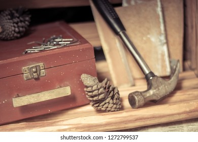 Diy inspiration with a brown wooden box, a metal hammer, nails, pine cones and wooden blocks.
