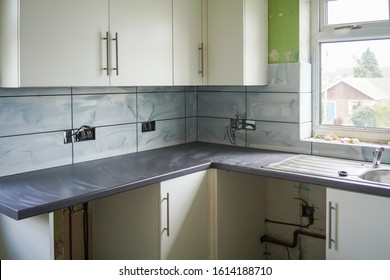 A DIY kitchen installation with white tiles and cupboards, grey grout and grey work surface. The unfinished tiles are smeared with grout and new electrical socket wires are exposed. Work in progress.