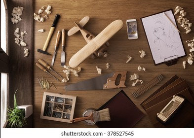 DIY project at home concept, work table with handmade wooden toy airplane and carpentry work tools, top view