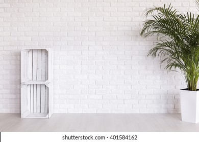 DIY regale made from wood boxes and plant in decorative plant standing in white interior with light flooring and brick wall
