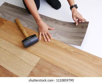 DIY and renovation concept : woman hands installing vinyl wood floor to covered on ceramic tile