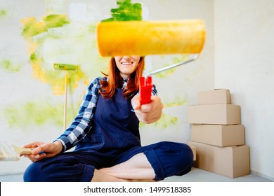 DIY repair,everything is possible concept. Funny female worker in overall holding a roller and brush paint for the walls trying to color you making a repair in home on abstract colorful background.