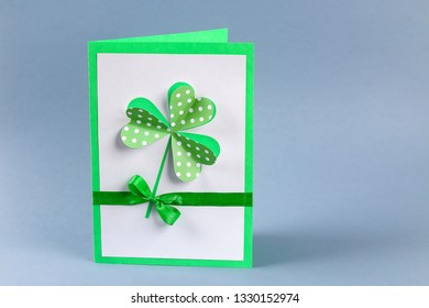 Diy St. Patricks Day greeting card made of cardboard and paper clovers on a gray background. Gift idea, decor Spring, Patrick Day. Step by step. Top view. Process kid children craft.