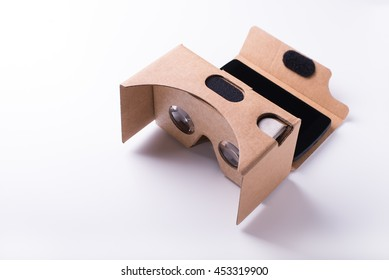 DIY virtual reality headset. Assembled from pre-cut cardboard and bi-convex lenses. Isolated over a white background with a smartphone attached.