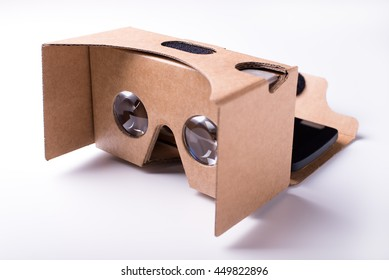 DIY virtual reality headset. pre-cut cardboard and lenses. isolated over a white background with a smartphone.