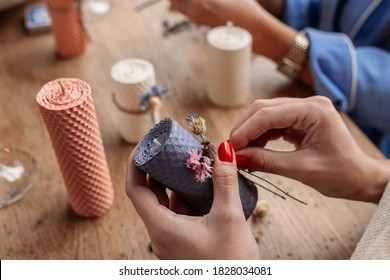 DIY wax candle making process. Woman making decorative wax candle and decorates with dried flowers, close-up of hands