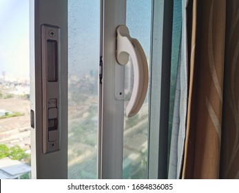 DIY white PVC plastic window made from broken jug and used shaft pitcher for handle open and close window, With blurred real environment background.