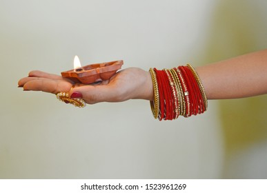 Diya in hand with beautifull bangles and lamps, Indian festival, Diwali