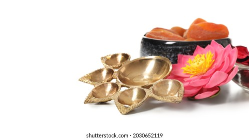 Diya lamp with lotus flower and treats for celebration of Divaly on white background