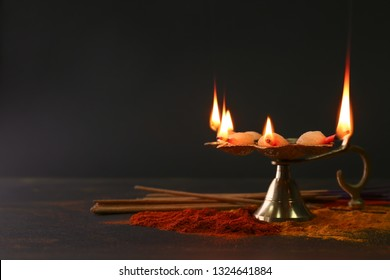 Diya lamp with spices for celebration of Divaly on dark background