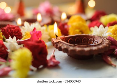 diya lamps lit during diwali celebration with flowers and sweets in background
