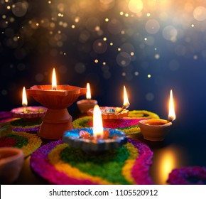 Diya lamps lit on colorful rangoli during Diwali celebration