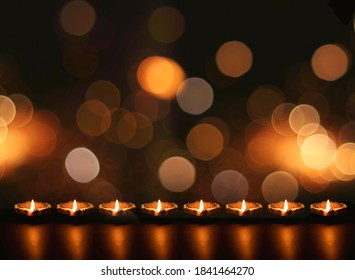 Diya lamps on a reflective base with glittering bokeh