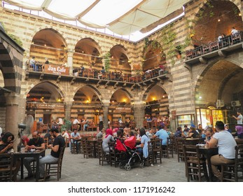 DIYARBAKIR, TURKEY - 25 AUG 2018: View of the Hasanpasa Khan medieval historic building where people have breakfast and small shops, the central of Diyarbakir,