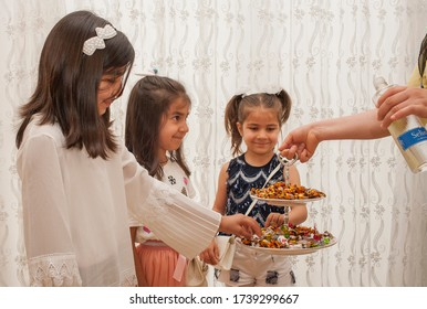 DIYARBAKIR- TURKEY- MAY 24, 2020: sugar is served to children at Ramadan festivals in Turkey. And cologne is poured into their hands