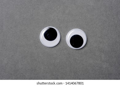 Dizzy googly eyes on grey background.