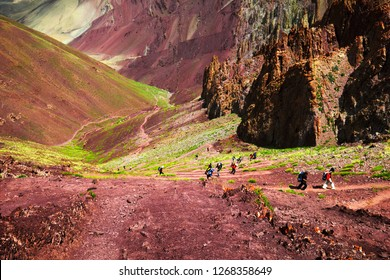 Dizzy nature scenery: few unidentified people climbing through mountain pass between colorful slopes in Himalayas, vicinity of Rumbak village, Leh district, Ladakh range, Jammu & Kashmir, India