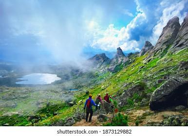 Dizzy nature scenery: group of unidentified people climbing through high mountain pass between peaked rocks, green valley and lake in Ergaki national park, Sayan, Krasnoyarsk region, Siberia, Russia