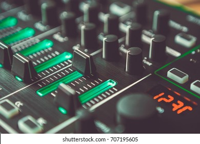 Dj audio mixer in closeup.Volume regulator knob in macro.Audio channel playing on maximum level.Dj audio equipment for party set.Stage equipment for concert.Mix music,play popular songs at club party