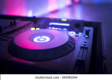 DJ console cd mp4 deejay mixing desk Ibiza house music party in nightclub with colored disco lights.