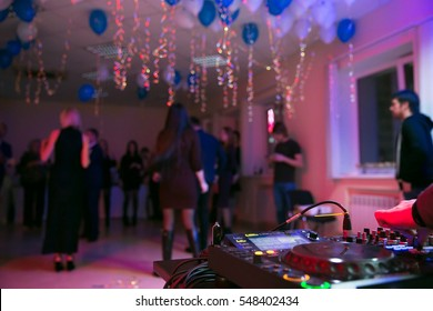 DJ console with people dancing and blue baloons on blurred background