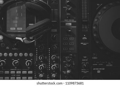 DJ control panel. Upper view closeup of dj musical mixer professional console black color with many buttons and knobs and glamour headphones with pastes in night club or studio on digital background