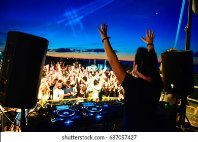 Dj and dance floor with hands to the sky during a beach party at sunrise. Emotions for the sound explosion at music festival. The view is from behind the consolle on the stage