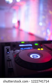 DJ deejay mixing desk equipment in wedding receoption party disco with color discotheque lights.