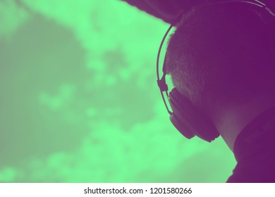 DJ deejay producer wearing closed headphones listening to music in artistic photo.