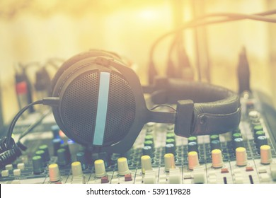 Dj equipment in a studio working with sound and light mixer console ,headphones resting on the top,boutique recording tools  desk,selective focus,vintage color