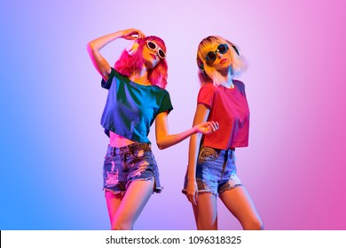 DJ Girl with Pink Blond Fashion neon Hairstyle Dance. Two Young carefree Hipster enjoy music in summer Trendy outfit. Sexy fashionable woman. Night Clubbing dancing concept. Creative Art neon