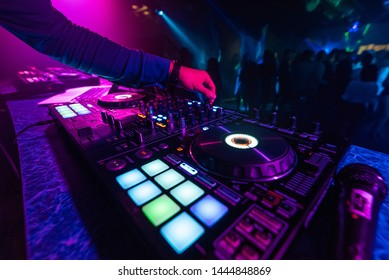 DJ hand plays a professional mixer at a nightclub party