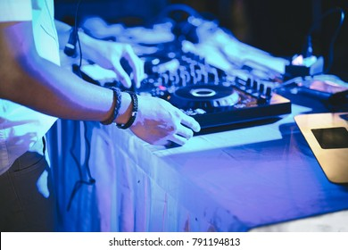 DJ hands on stage mixing, disc jockey and mix tracks on sound mixer controller, playing music for party at night club.