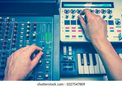 DJ hands remixed dance music on professional sound engineering equipment
