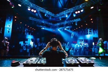 DJ with headphones at night club party under the blue light and people crowd in background