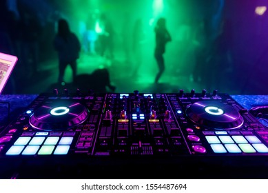 DJ mixer in the booth on the background of the dance floor with dancing people
