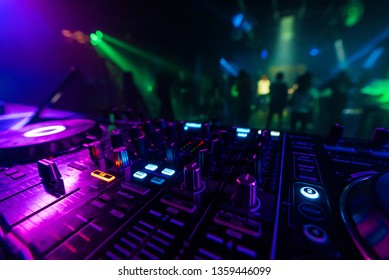 DJ mixer controller Board for professional mixing of electronic music in a nightclub at a party with dancing people in the background
