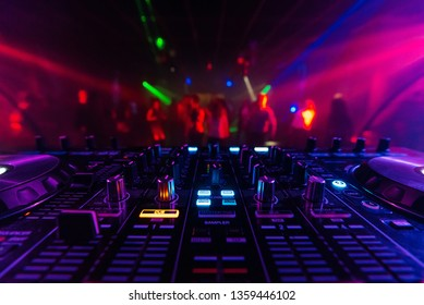 DJ mixer controller Board for professional mixing of electronic music in a nightclub at a party with dancing people