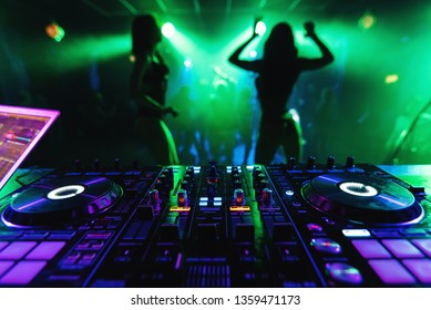 DJ mixer controller in a nightclub with dancing on the background of go-go dance girls at a party