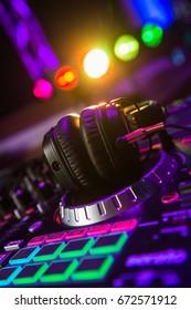 Dj mixer with headphones at a nightclub, music
